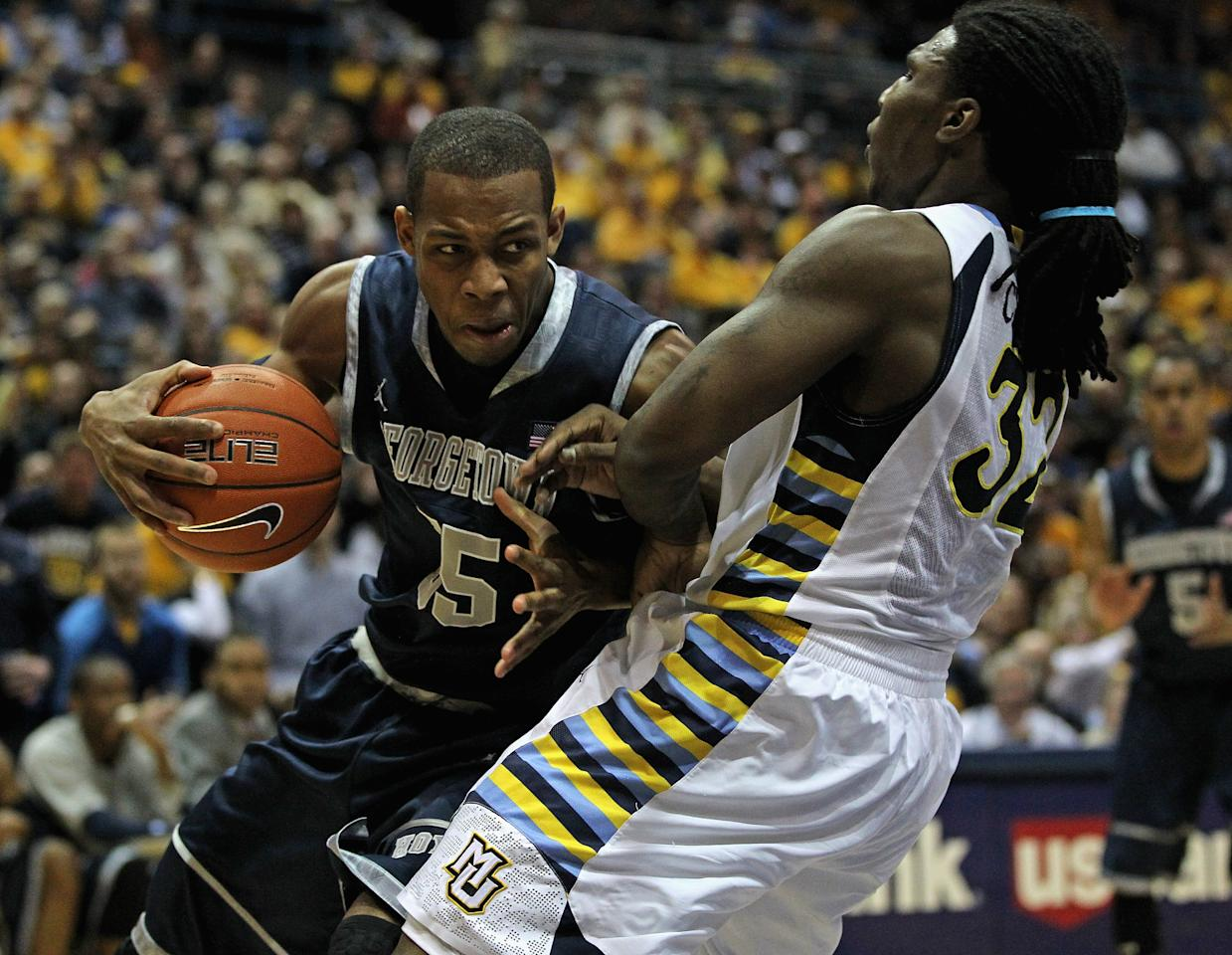 MILWAUKEE, WI - MARCH 03:  Jabril Trawick #55 of the Georgetown Hoyas charges against Jae Crowder #32 of the Marquette Golden Eagles at the Bradley Center on March 3, 2012 in Milwaukee, Wisconsin. Marquette defeated Georgetown 83-69.  (Photo by Jonathan Daniel/Getty Images)