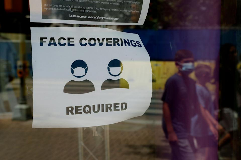 A visitor wearing a mask to protect against the spread of COVID-19 passes a sign requiring masks in San Antonio, Texas. (Photo: ASSOCIATED PRESS)
