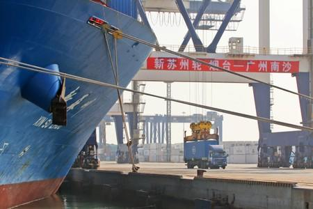 Crane lifts a container from a truck next to a cargo vessel at a port in Yantai, Shandong