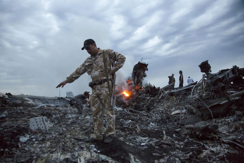 FILE - In this July 17, 2014 file photo, people walk amongst the debris at the crash site of a passenger plane near the village of Grabovo, Ukraine. The Dutch foreign minister said Thursday Feb. 7, 2019, that the Netherlands is in diplomatic discussions with Russia about his country's assertion that Moscow bears legal responsibility for the downing of a Malaysian passenger jet over Ukraine in 2014. (AP Photo/Dmitry Lovetsky, File)