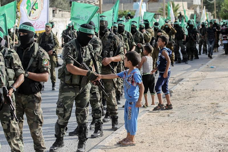 Palestinian children greet fighters from the armed wing of Islamist movement Hamas in the Gaza Strip on July 20, 2017