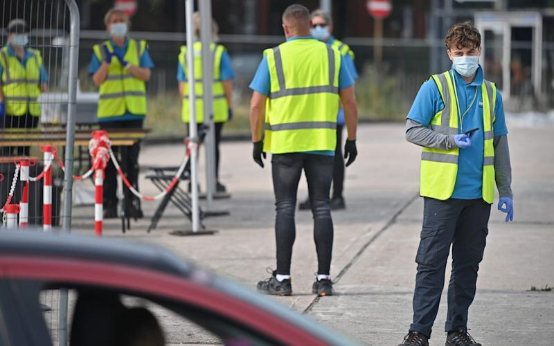 Workers wear NHS Test and Trace branded Hi-Vis jackets as they work at a COVID-19 testing centre in Bolton, - PAUL ELLIS