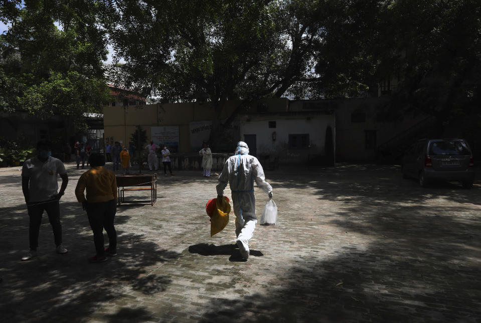 A health worker arrives at a makeshift center in a school to conduct tests for COVID-19 in New Delhi, India, Tuesday, Sept. 1, 2020. India has now reported more than 75,000 infections for five straight days, one of the highest in the world, just as the government began easing restrictions to help the battered economy. (AP Photo/Manish Swarup)