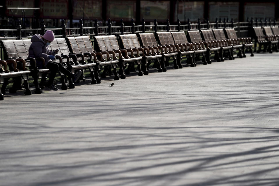 A woman wearing a face mask to help curb the spread of the coronavirus takes a rest on the bench at the Forbidden City in Beijing, Sunday, Jan. 10, 2021. More than 360 people have tested positive in a growing COVID-19 outbreak south of Beijing in neighboring Hebei province. (AP Photo/Andy Wong)