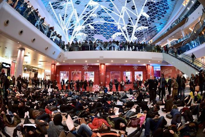 """A group of protesters create a """"die-in"""" at the Westfield shopping mall in West London on December 10, 2014, in support of protests in the US over the killings of black suspects by white police officers (AFP Photo/Leon Neal)"""