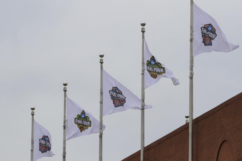 Final Four flags fly over the national office of the NCAA in Indianapolis, Thursday, March 12, 2020. The major conferences in college sports have canceled their basketball tournaments because of the new coronavirus, putting the celebrated NCAA college basketball ournament in doubt. (AP Photo/Michael Conroy)