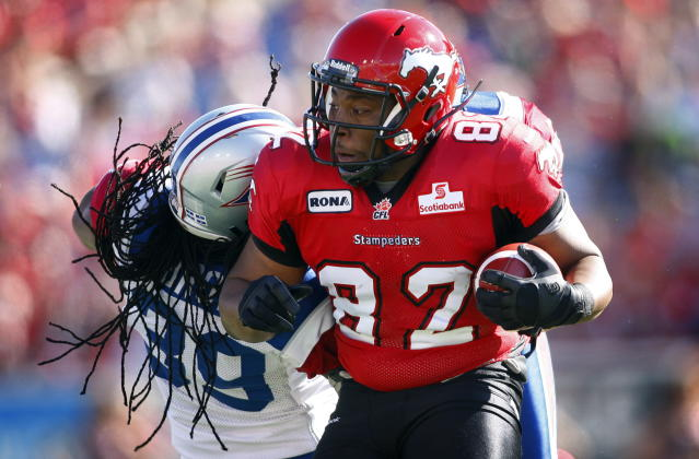 Montreal Alouettes' Jerald Brown, left, tries to tackle Calgary Stampeders' Nik Lewis during first half CFL football action in Calgary, Alta., Sunday, July 1, 2012. THE CANADIAN PRESS/Jeff McIntosh