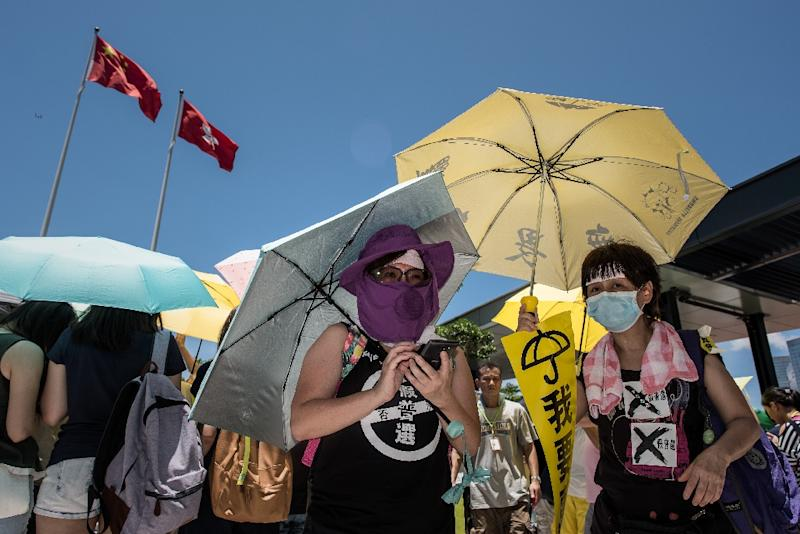 Hong Kong pro-democracy supporters stand outside the city's legislature on June 18, 2015 (AFP Photo/Philippe Lopez)