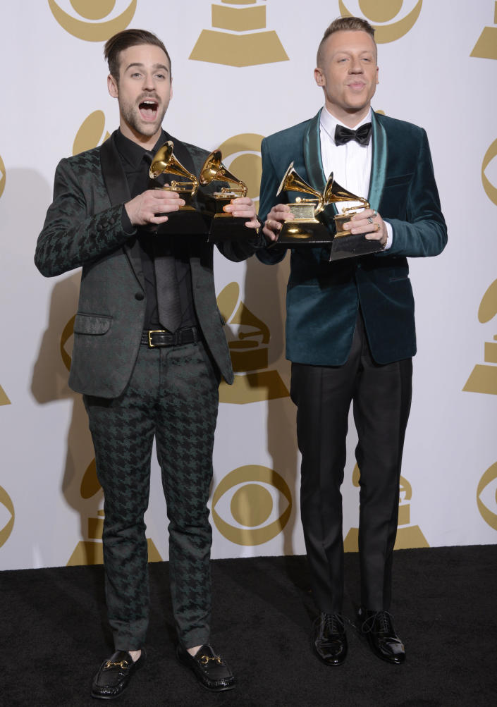 """FILE - Ryan Lewis, left, and Macklemore pose with their awards for best rap performance and best rap song, for """"Thrift Shop,"""" best rap album for """"The Heist"""" and best new artist at the 56th annual Grammy Awards in Los Angeles on Jan. 26, 2014. The Grammy Awards are in discussion to remove its nomination review committees — the group that determines the contenders for key awards at the coveted music show. (Photo by Dan Steinberg/Invision/AP, File)"""