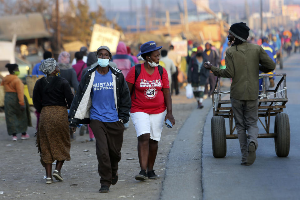 People wear face masks to protect against coronavirus, in Harare, Monday, Sept. 21, 2020. As Zimbabwe's coronavirus infections decline, strict lockdowns designed to curb the disease are being replaced by a return to relatively normal life. The threat has eased so much that many people see no need to be cautious, which has invited complacency. (AP Photo/Tsvangirayi Mukwazhi)
