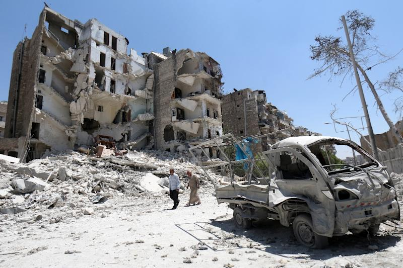 Syrian men walk amid rubble and debris in the Qadi Askar district of Aleppo on July 5, 2015 as the regime steps up air attacks in the province