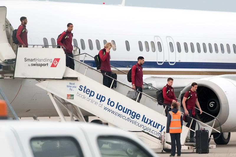 Liverpool players including Loris Karius, pictured with his hand over his face, get off their plane home at Liverpool's John Lennon airport: PA