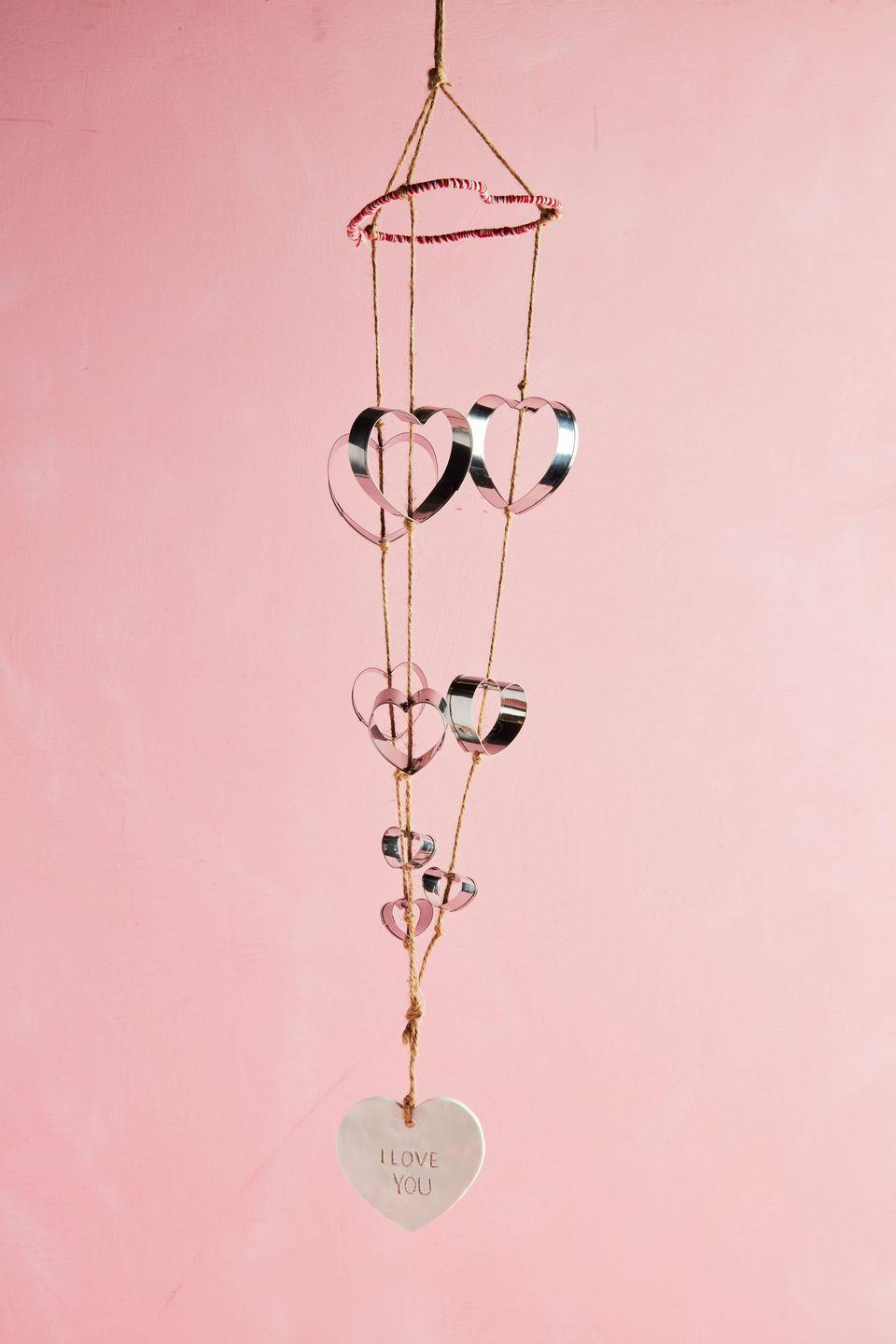 """<p>Transform humble cookie cutters into cheery wind chimes that are ideal for hanging above a bed or on the front porch.<strong><br></strong></p><p><strong>To make:</strong> Fashion a 10- to 12-inch length of wire into a heart shape; wrap with red twine, set aside. Make a clay heart with <a href=""""https://www.amazon.com/POZEAN-Modeling-Sculpting-Accessories-Beginners/dp/B07XXWXBDP/ref=sr_1_1_sspa"""" rel=""""nofollow noopener"""" target=""""_blank"""" data-ylk=""""slk:oven-baked modeling clay"""" class=""""link rapid-noclick-resp"""">oven-baked modeling clay</a>; punch a hole in the top for hanging and write a phrase (if desired) before baking, and set aside. Punch holes in the crook and point of 3 large, 3 medium, and 3 small heart-shaped cookie cutters. Cut three lengths of twine. Working with one length at a time, thread a large, medium, and small cookie cutter onto twine, knotting above and below each cutter so that it stays in place. Repeat with remaining twine and cookie cutters. Wrap twine lengths (making sure the hearts are facing the correct direction) around wire heart; gather twine lengths at the top and tie in a knot for hanging. Knot twine lengths at the bottom and trim. Thread a short length of twine through the ceramic heart and tie to knot at the bottom of the wine chime, and hang.</p><p><a class=""""link rapid-noclick-resp"""" href=""""https://www.amazon.com/Ann-Clark-Cookie-Cutters-5-Piece/dp/B07ZDHJDKJ/ref=sr_1_4_sspa?tag=syn-yahoo-20&ascsubtag=%5Bartid%7C10050.g.2971%5Bsrc%7Cyahoo-us"""" rel=""""nofollow noopener"""" target=""""_blank"""" data-ylk=""""slk:SHOP COOKIE CUTTERS"""">SHOP COOKIE CUTTERS</a></p>"""