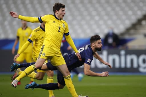 France's Olivier Giroud, background, scores his side's third goal during the UEFA Nations League soccer match between France and Sweden at the Stade de France stadium in Saint-Denis, northern Paris, Tuesday, Nov. 17, 2020. (AP Photo/Francois Mori)