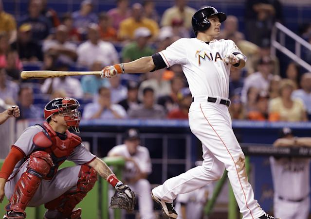 Miami Marlins' Derek Dietrich, right, watches after hitting a three-run home run as Washington Nationals catcher Jose Lobaton, left, looks on during the fourth inning of a baseball game, Wednesday, April 16, 2014, in Miami. (AP Photo/Lynne Sladky)