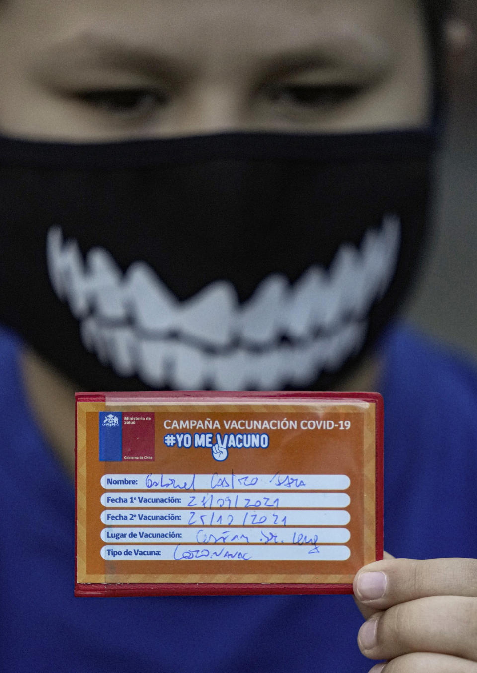 A child shows his vaccination card after getting a dose of the Coronavac COVID-19 vaccine at his school in Santiago, Chile, Monday, Sept. 27, 2021, during the start of vaccinations in schools for children between ages 6 to 11. (AP Photo/Esteban Felix)
