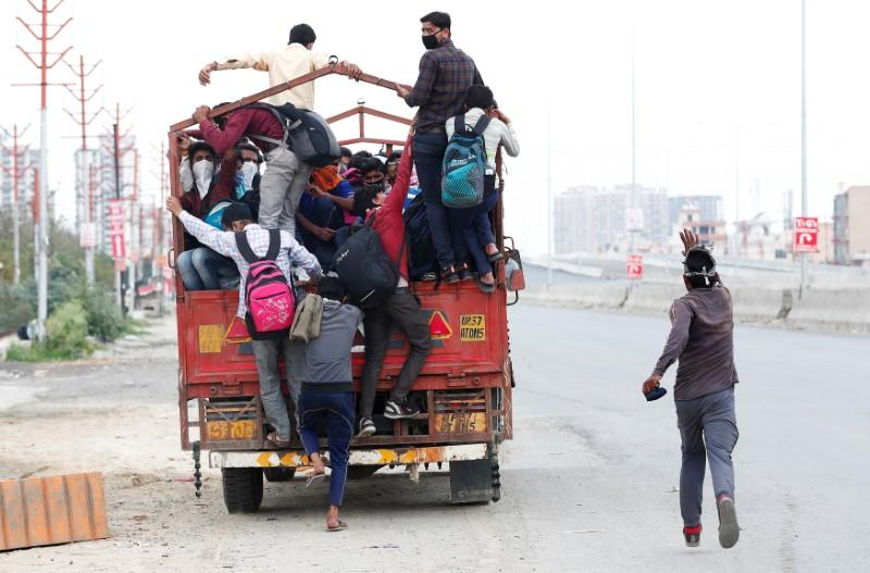 A migrant worker runs behind a truck as others try to board it to return to their villages after India ordered a 21-day nationwide lockdown to limit the spreading of coronavirus disease (COVID-19), in Ghaziabad