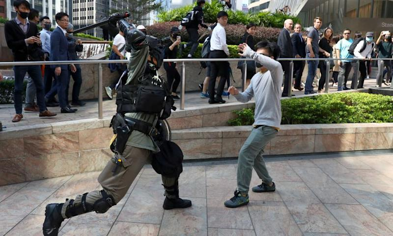 A riot police officer clashes with a protester in Hong Kong's central district as workers look on.