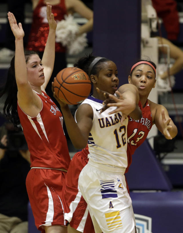 Albany guard Imani Tate (12) is guarded by Stony Brook players Brittany Snow, left, and Sabre Proctor (13) during the first half of an NCAA America East college championship basketball game on Monday, March 10, 2014, in Albany, N.Y. (AP Photo/Mike Groll)