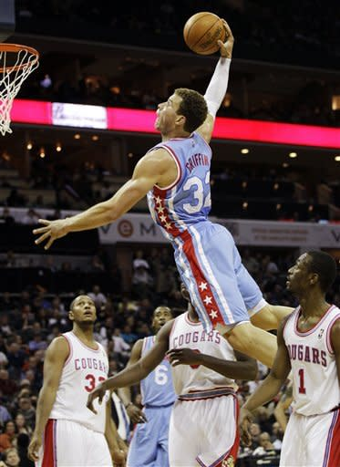 Los Angeles Clippers' Blake Griffin (32) goes up to dunk as Charlotte Bobcats' Kemba Walker (1), Bismack Biyombo (0), and Boris Diaw (32) look on during the second half of an NBA basketball game in Charlotte, N.C., Saturday, Feb. 11, 2012. (AP Photo/Chuck Burton)