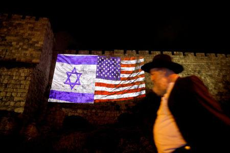 A man walks by as the Israeli national flag and an American one are projected on a part of the walls surrounding Jerusalem's Old City December 6, 2017. REUTERS/Ronen Zvulun