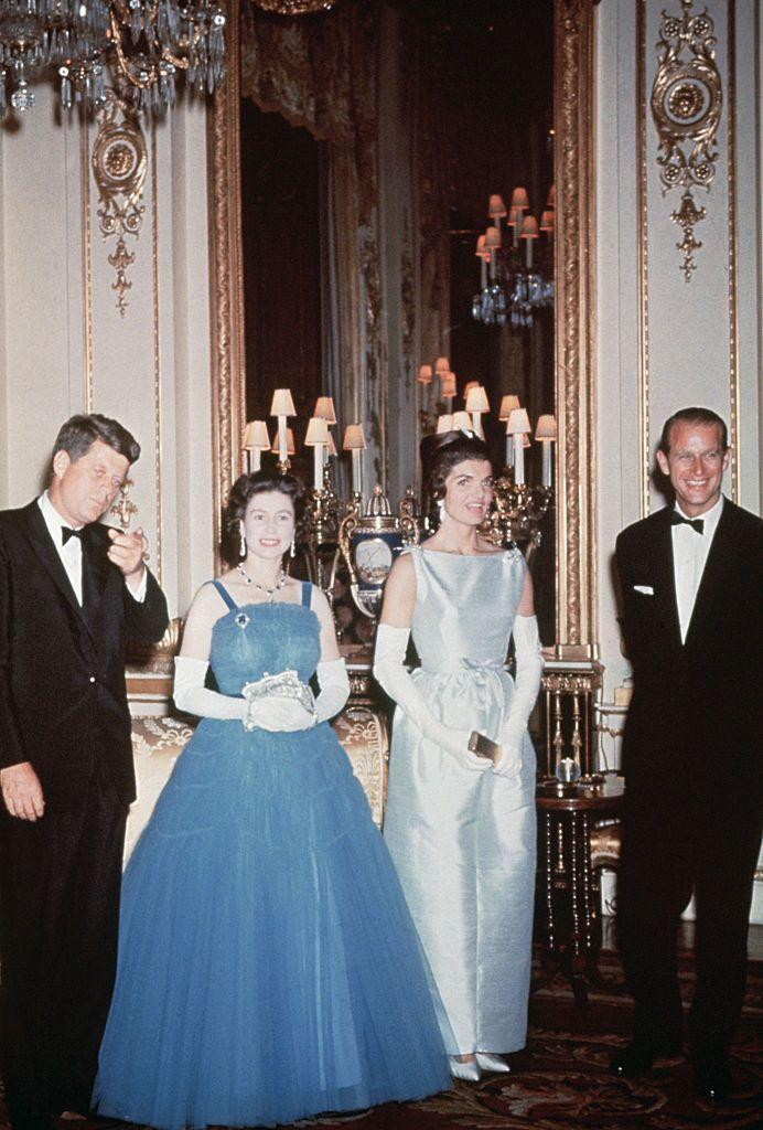 """<p>American royalty met actual royalty when President John F. Kennedy and<a href=""""https://www.townandcountrymag.com/society/tradition/a13128840/john-kennedy-jackie-kennedy-queen-elizabeth-meeting-buckingham-palace/"""" rel=""""nofollow noopener"""" target=""""_blank"""" data-ylk=""""slk:Jackie Kennedy visited Buckingham Palace"""" class=""""link rapid-noclick-resp""""> Jackie Kennedy visited Buckingham Palace</a> for the first time. The Queen wore a blue ballgown by Norman Hartnell with white gloves for the occasion.</p>"""