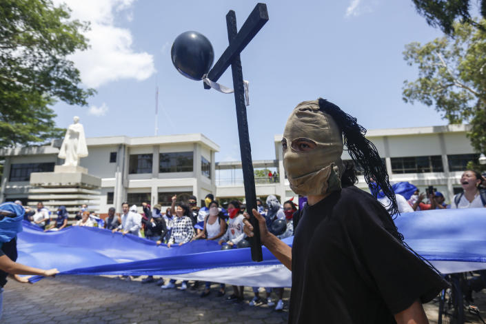 Students hiding their identify for fear of being identified and later attacked by security forces or government supporters protest inside the Central American University (UCA) to demand the release of all political prisoners, on the last day of a 90-day period for releasing such prisoners as part of negotiations between the government and opposition, in Managua, Nicaragua, Tuesday, June 18, 2019. Nicaragua's government said Tuesday that it has released all prisoners detained in relation to 2018 anti-government protests, though the opposition maintains that more than 80 people it considers political prisoners are still in custody. (AP Photo/Alfredo Zuniga)