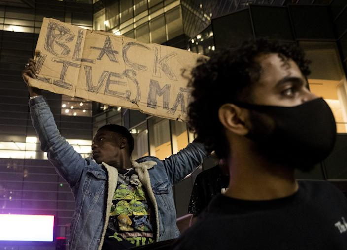 A protester holds up a sign during a night of clashes in downtown Detroit.