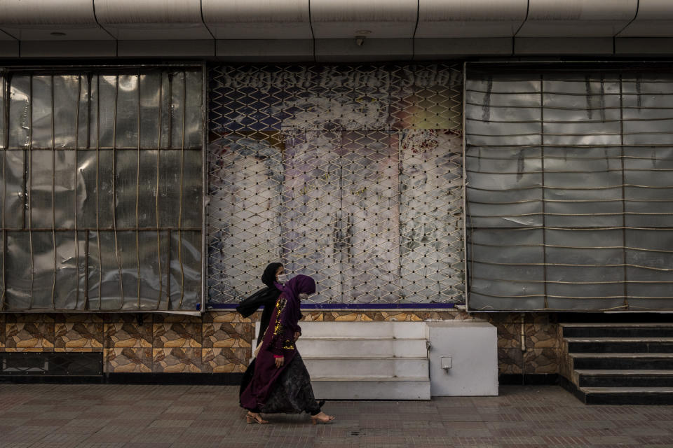 Afghan women walk past a closed beauty salon in Kabul, Afghanistan, Saturday, Sept. 11, 2021. Since the Taliban gained control of Kabul, several images depicting women outside beauty salons have been removed or covered up. (AP Photo/Bernat Armangue)