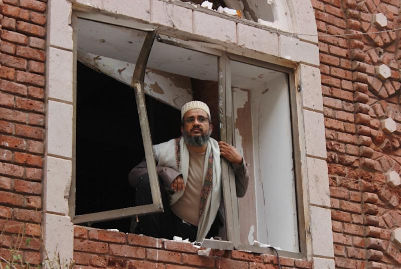 A Yemeni man looks from a damaged window at the site of a car bomb explosion near a mosque on July 29, 2015 in the capital Sanaa (AFP Photo/Mohammed Huwais)