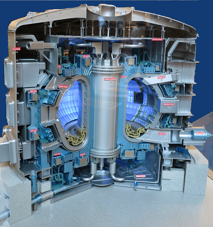 A cutaway illustration of a massive metal structure with a cylindrical core surrounded by a hollow ring filled with blue light