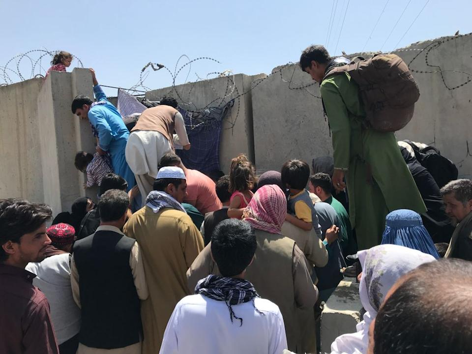 People struggle to cross the boundary wall of Hamid Karzai International Airport to flee the country. Source: Getty