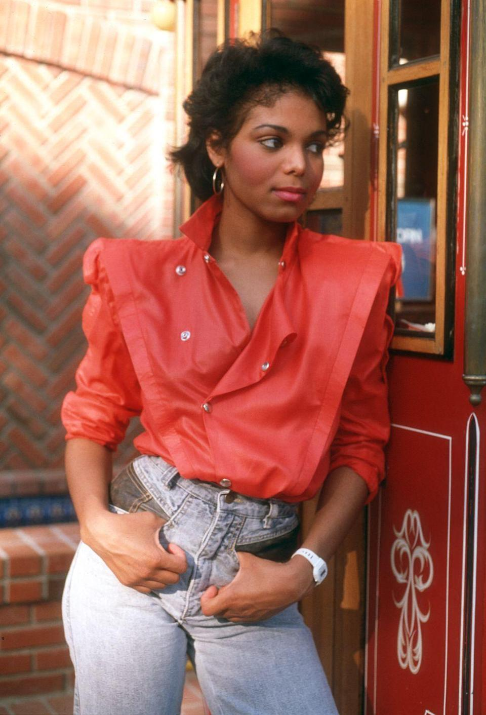 <p>Janet Jackson embraces power shoulders in a red top tucked into high-waisted denim. </p>