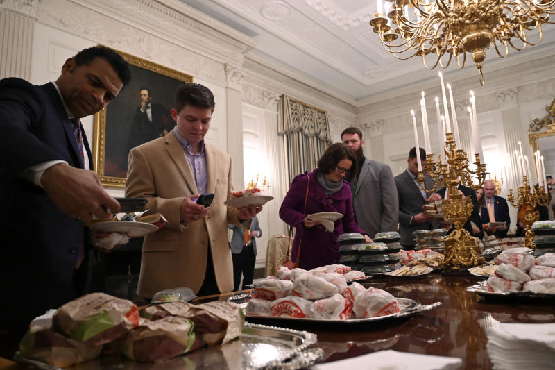FILE - In this Jan. 14, 2019, file photo, guests attending a reception for the Clemson NCAA college football team grab fast food sandwiches in the State Dining Room of the White House in Washington. (AP Photo/Susan Walsh, File)