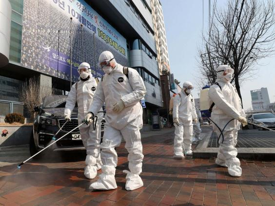 Workers wearing protective gears spray disinfectant on Daegu's deserted streets (Kim Jun-beom/Yonhap via AP)