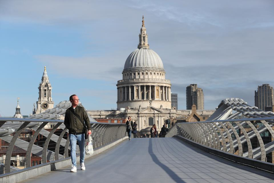 A commuter crosses a near-empty Millennium Bridge in London, the day after Prime Minister Boris Johnson called on people to stay away from pubs, clubs and theatres, work from home if possible and avoid all non-essential contacts and travel in order to reduce the impact of the coronavirus pandemic.