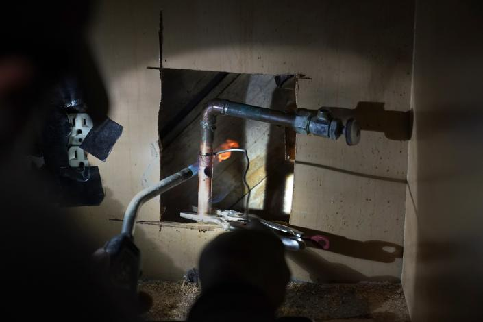 CORRECTS SPELLING OF LAST NAME TO VALERIO, NOT VALERIA - Handyman Roberto Valerio works on repairing a broken pipe beneath the sink in the home of Nora Espinoza, on Saturday, Feb. 20, 2021, in Dallas. The pipe broke during freezing temperatures brought by last week's winter weather. (AP Photo/Tony Gutierrez)