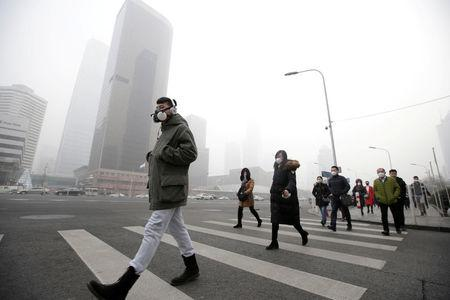 FILE PHOTO: A man wearing a respiratory protection mask walks toward an office building during the smog after a red alert was issued for heavy air pollution in Beijing's central business district, China, December 21, 2016. REUTERS/Jason Lee/File Photo