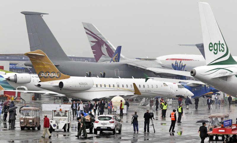 Visitors walk among planes displayed at the 50th Paris Air Show at Le Bourget airport, north of Paris, Wednesday June 19, 2013. Visible at foreground is a Bombardier Global 6000 jet.(AP Photo/Remy de la Mauviniere)