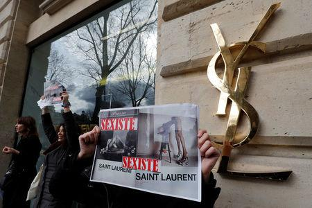 "Activists hold placards which read ""Sexist"" during a demonstration in front of a Yves Saint Laurent shop in Paris"