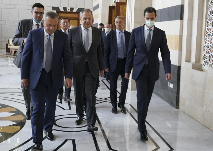 In this photo released on the official Facebook page of the Syrian Presidency, shows Syrian President Bashar Assad, right, wearing a mask to help prevent the spread of the coronavirus, walks with Russian Foreign Minister Sergey Lavrov, center, and Deputy Prime Minister Yuri Borisov, left, in Damascus, Syria, Monday, Sept. 7, 2020. Lavrov met with Syrian President Bashar Assad shortly after landing in the Syrian capital on his first visit since 2012. (Syrian Presidency via Facebook)