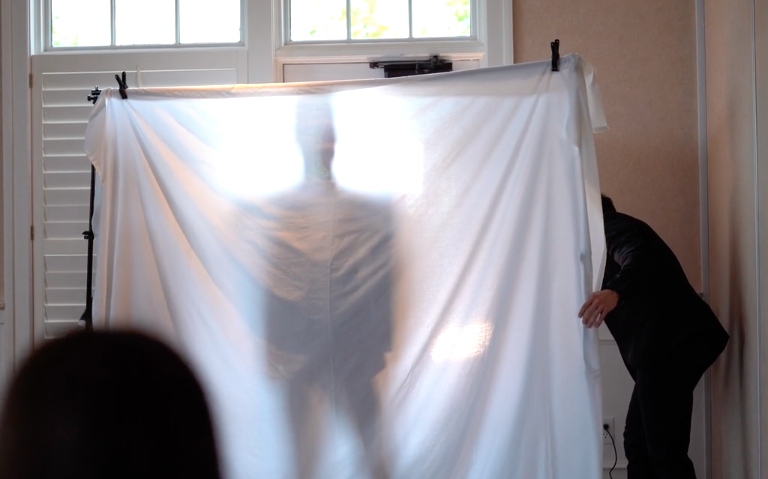 A still from the video released from The LDS Millionaire Matchmaking event featuring the mystery bachelor behind a sheet. Image via Vimeo.