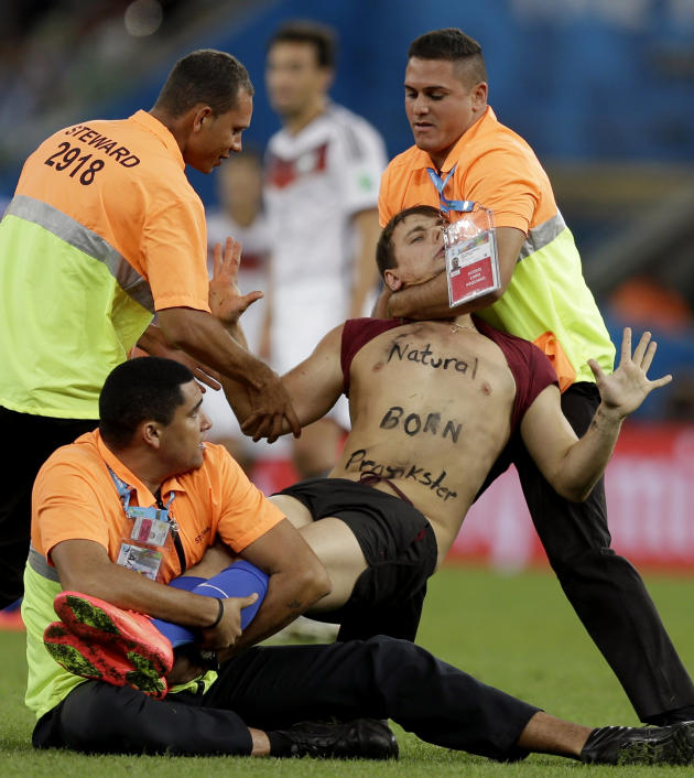 A spectator who ran on to the pitch during the World Cup final soccer match between Germany and Argentina is subdued by security personnel at the Maracana Stadium in Rio de Janeiro, Brazil, Sunday, July 13, 2014. (AP Photo/Natacha Pisarenko)