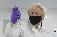 Britain's Prime Minister Boris Johnson looks at a pipette before him, during briefing by a molecular biologist at the QuantuMDx Biotechnology company in Newcastle, England on Saturday Feb.13, 2021. Johnson is visiting manufacturing facilities in north east England to see ongoing Covid-19 responses in the region. (Ian Forsyth/Pool via AP)
