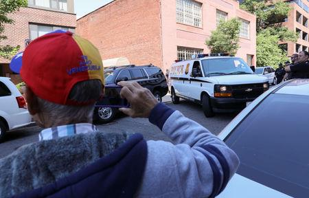 """A man with the phrase """"Te Amo Venezuela"""" on the back of his hat takes a picture as a U.S. Secret Service van believed to contain activists sympathetic to embattled President Nicolas Maduro leaves the Venezuelan embassy to the United States after a raid by U.S. law enforcement agents removed and arrested the remaining activists who had been part of a multi-week occupation of the embassy in Washington, U.S., May 16, 2019. REUTERS/Jonathan Ernst"""