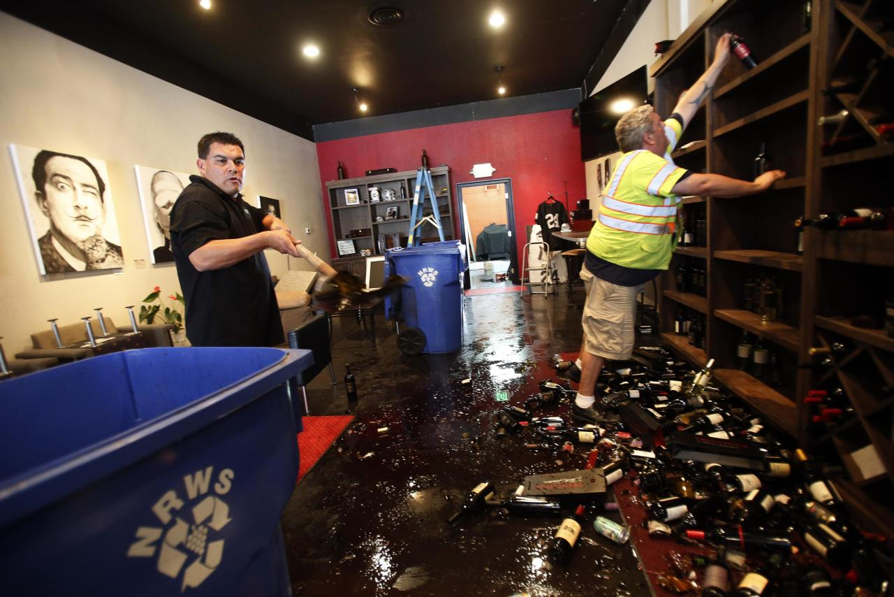 Rick Ruiz (L) and Tyler Paradise gather broken wine bottles from the floor of their Cult Following Wine Bar after an earthquake in Napa, California August 24, 2014. The 6.0 earthquake rocked wine county north of San Francisco early Sunday, injuring dozens of people, damaging historical buildings, setting some homes on fire and causing power outages around the picturesque town of Napa. REUTERS/Stephen Lam (UNITED STATES - Tags: DISASTER ENVIRONMENT)