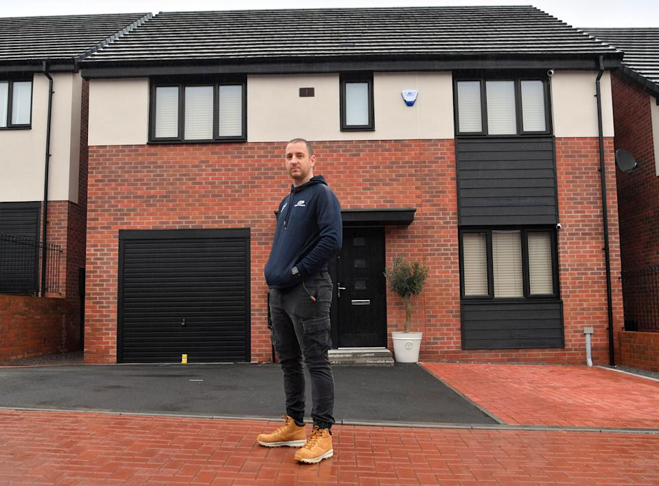 Andrew Higgs outside his rebuilt home in Cardiff. (Reach)