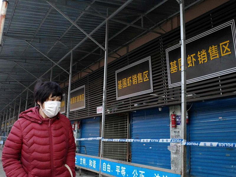 A woman walks in front of the closed Huanan wholesale seafood market, where health authorities say a man who died from a respiratory illness had purchased goods from, in the city of Wuhan: AFP via Getty Images