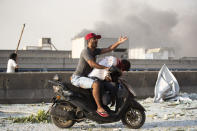 A man evacuates an injured person after a massive explosion in Beirut, Lebanon, Tuesday, Aug. 4, 2020. (AP Photo/Hassan Ammar)