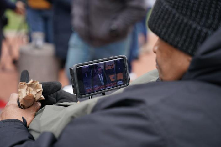 A man watches closing arguments on a small screen